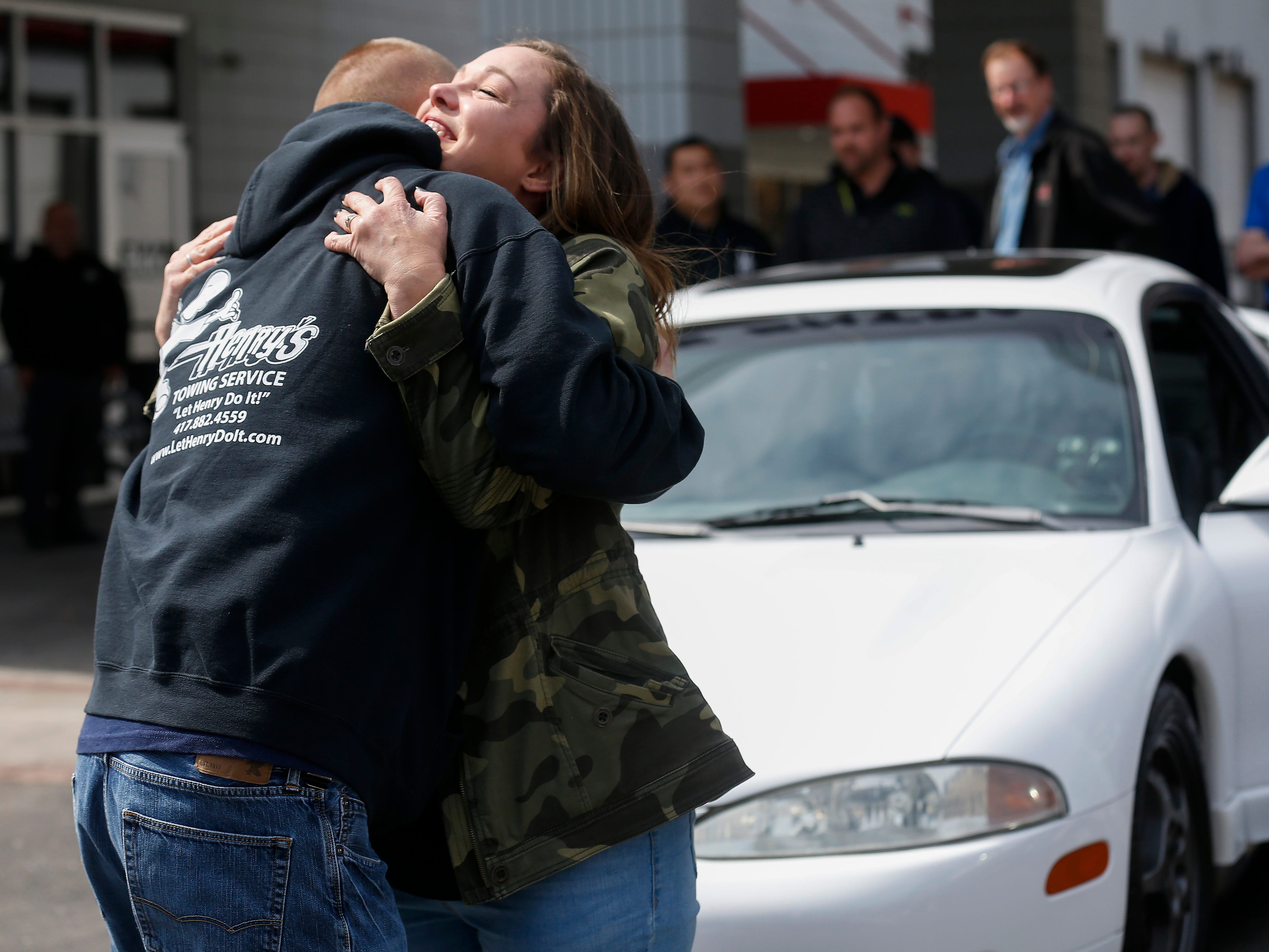 Kim Roberts, widow of Greene County Deputy Aaron Roberts, hugs Brian Bordwell, an operator at Henry's Towing, who was one of the community members who helped restore the 1995 Mitsubishi Eclipse that her husband was restoring.
