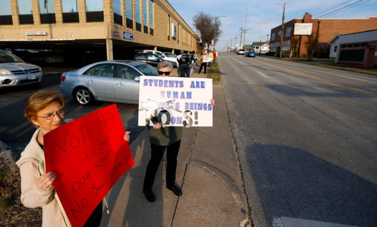 Mary Knapp (left) and Mary Byrne hold signs outside the Springfield Public School Kraft Administration Building on Tuesday, March 19, 2019, urging passerby's to vote no on Proposition S.
