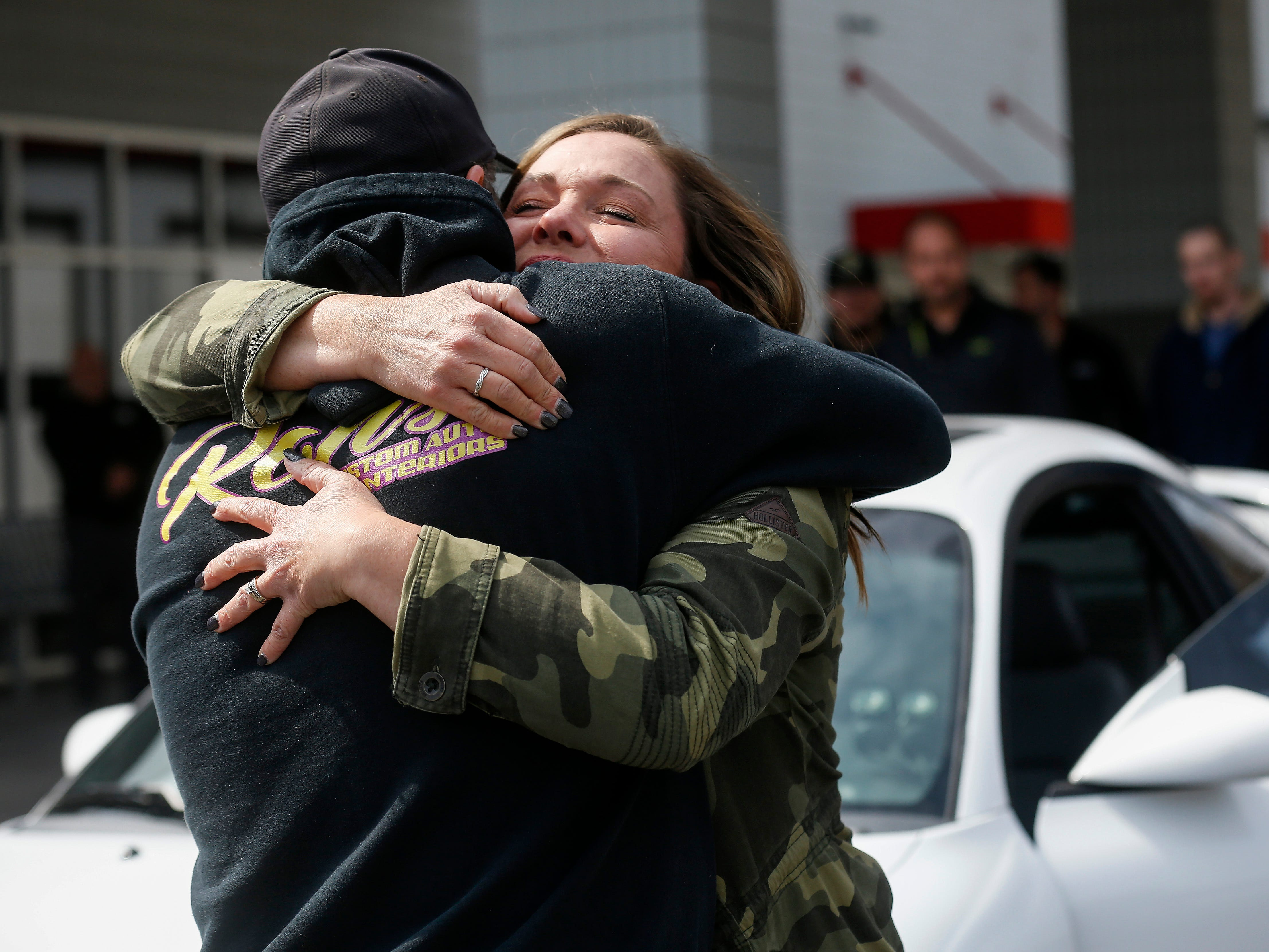 Kim Roberts, widow of Greene County Deputy Aaron Roberts, hugs Ron Stafford, owner of Ron's Custom Auto Interiors, who was one of the community members who helped restore the 1995 Mitsubishi Eclipse that her husband was restoring.