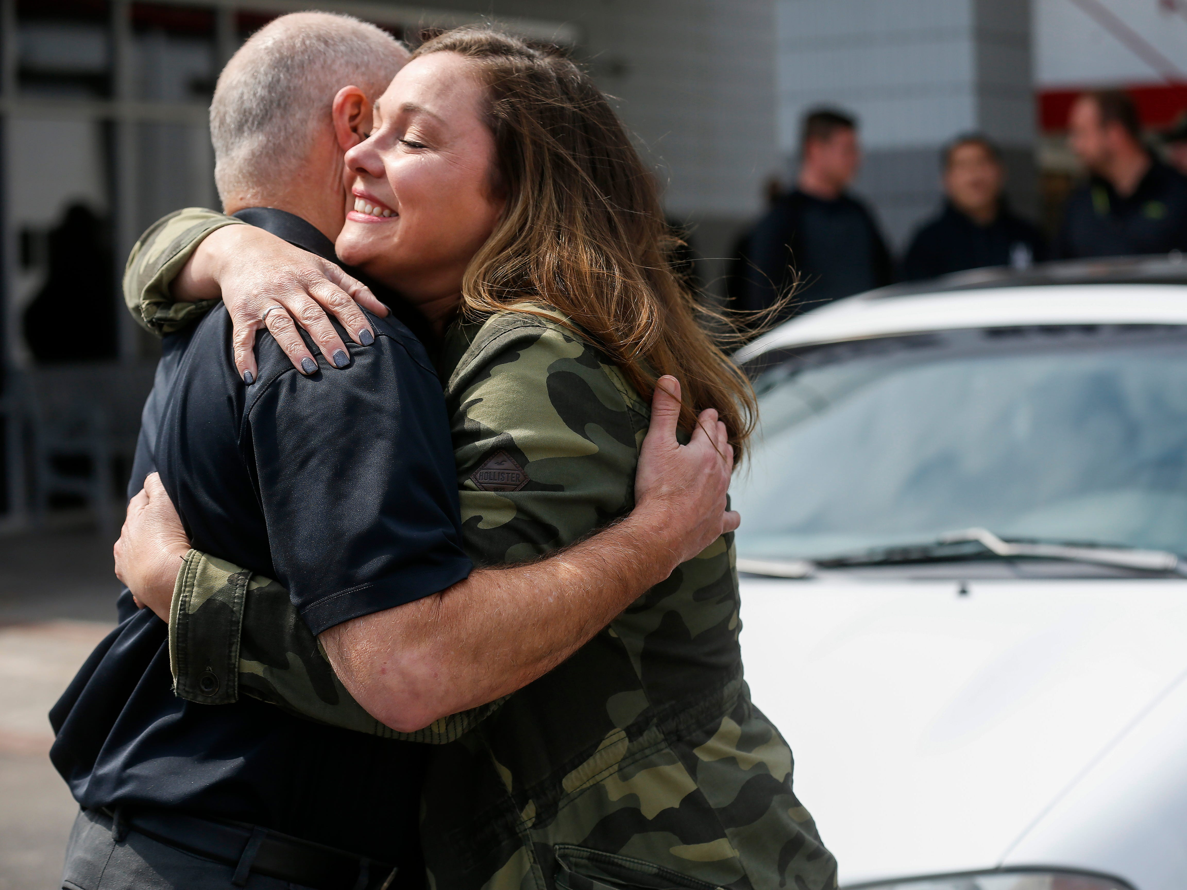 Kim Roberts, widow of Greene County Deputy Aaron Roberts, hugs Tim Cummings, executive vice president of Rick's Automotive, who was one of the community members who helped restore the 1995 Mitsubishi Eclipse that her husband was restoring.