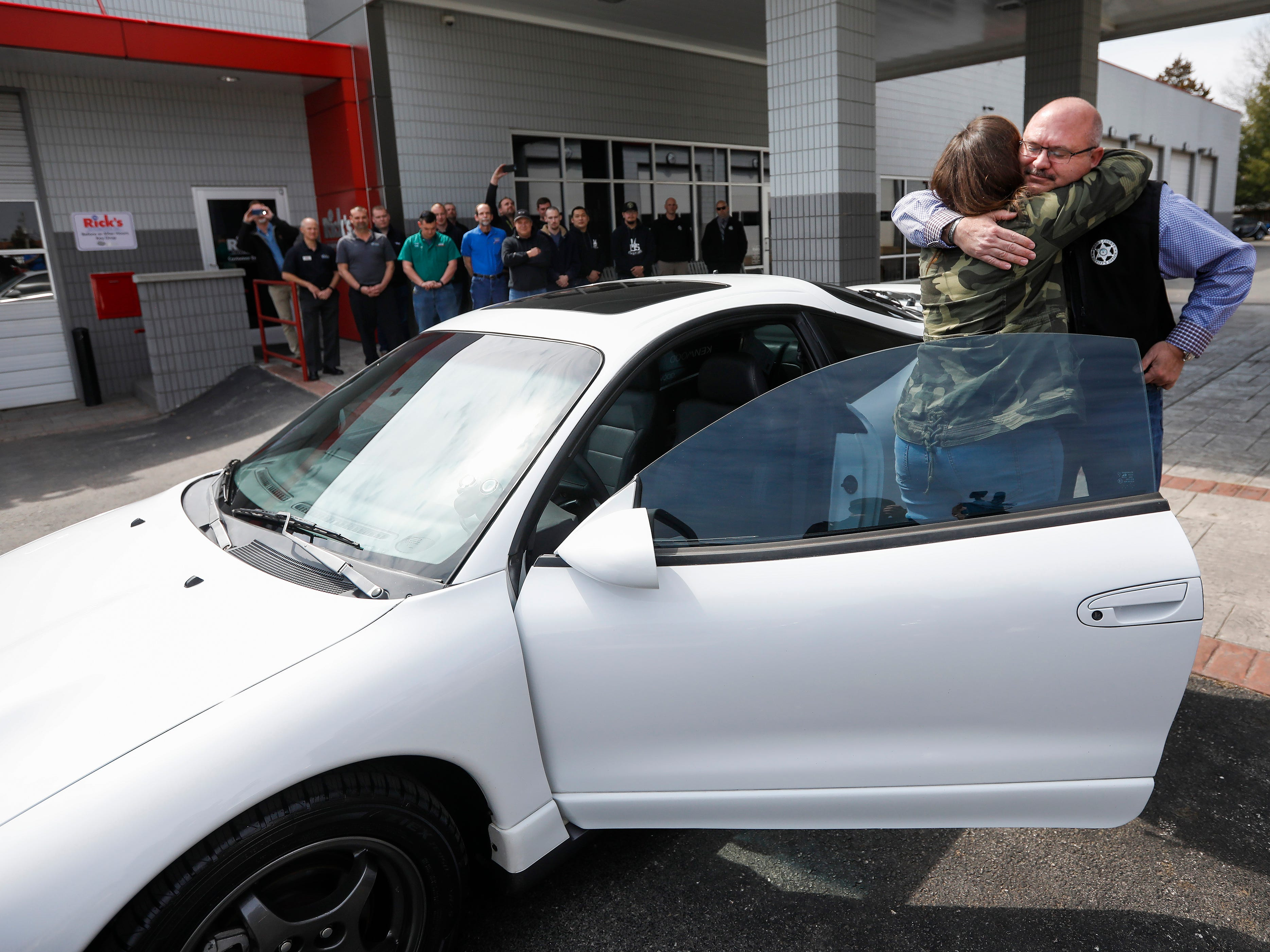 Kim Roberts, widow of Greene County Deputy Aaron Roberts, hugs Sheriff Jim Arnott after seeing the 1995 Mitsubishi Eclipse that her husband was restoring before he died.