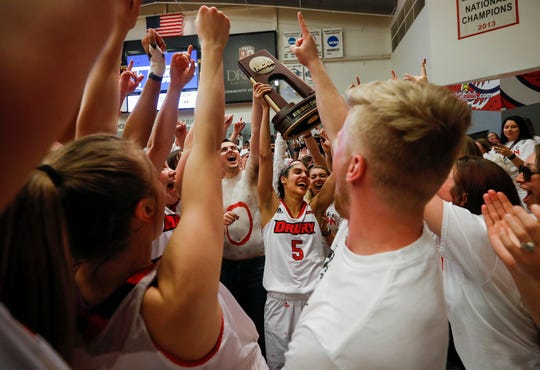 Daejah Bernard (5) raises the trophy and celebrates with Drury players and fans after winning the NCAA Division II Midwest Regional Championship game 51-44 over Grand Valley at the O'Reilly Family Event Center on Monday, March 18, 2019.