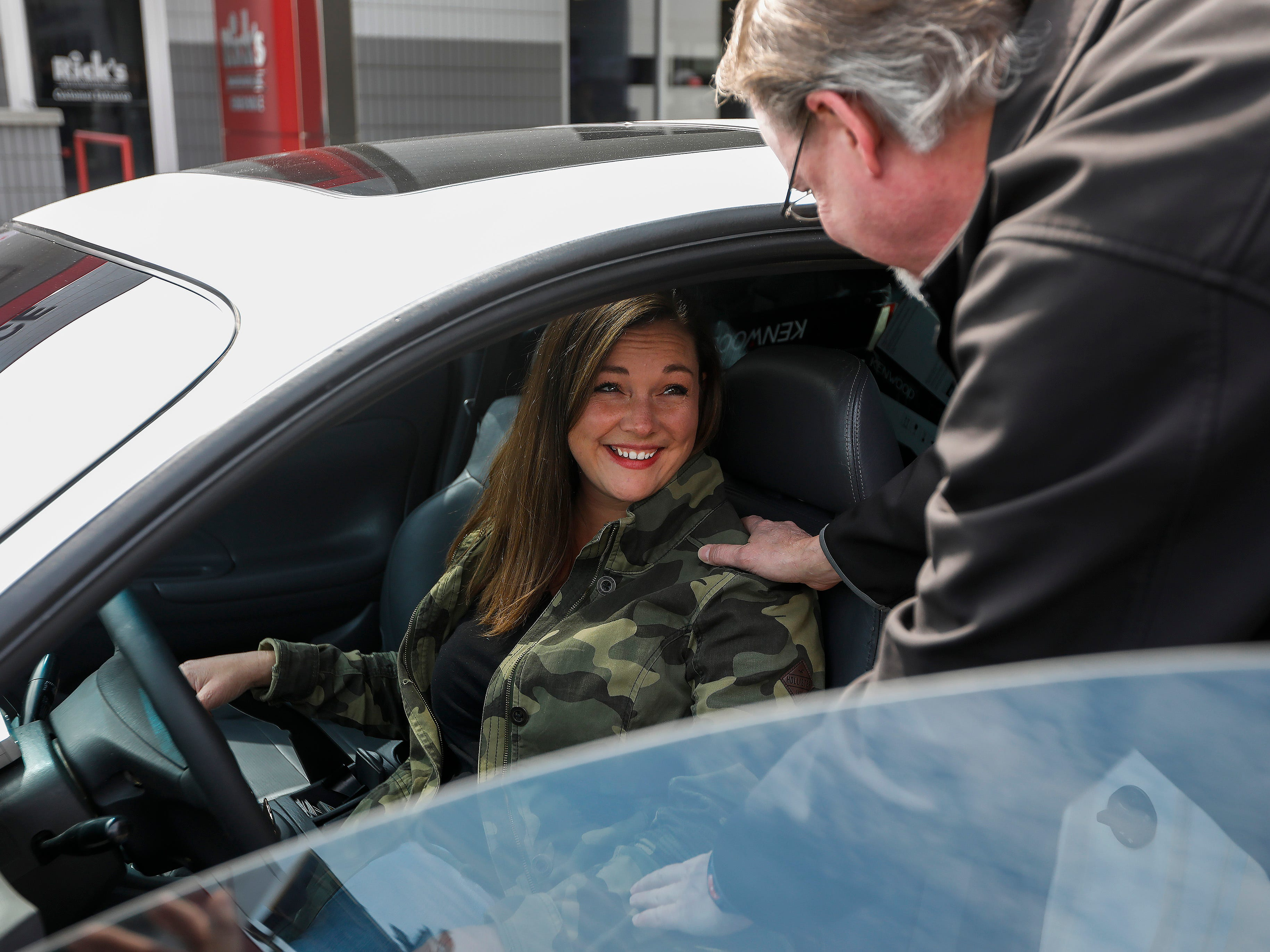 Kim Roberts, widow of Greene County Deputy Aaron Roberts, smiles as Andre Brunnert, manager at Car-fi, goes over the sound system that was installed in the 1995 Mitsubishi Eclipse that her husband was restoring before he died.