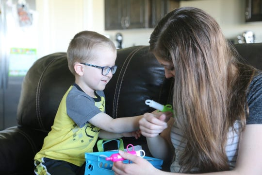 3-year-old Conner Alberts and his mom, Maggie Alberts, play with doctor toys in their St. George home.