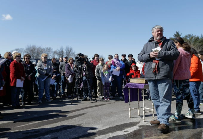 Pastor Tim O'Brien leads a vigil outside the Springs United Methodist Church on Tuesday, March 19, 2019, in Plover, Wis. The church was destroyed in a fire on Monday.