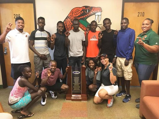 Darlene Moore (bottom right) poses with members of the cross country team and women's 2017 MEAC championship trophy. The FAMU women won the title in 2018 for the seventh year in row.