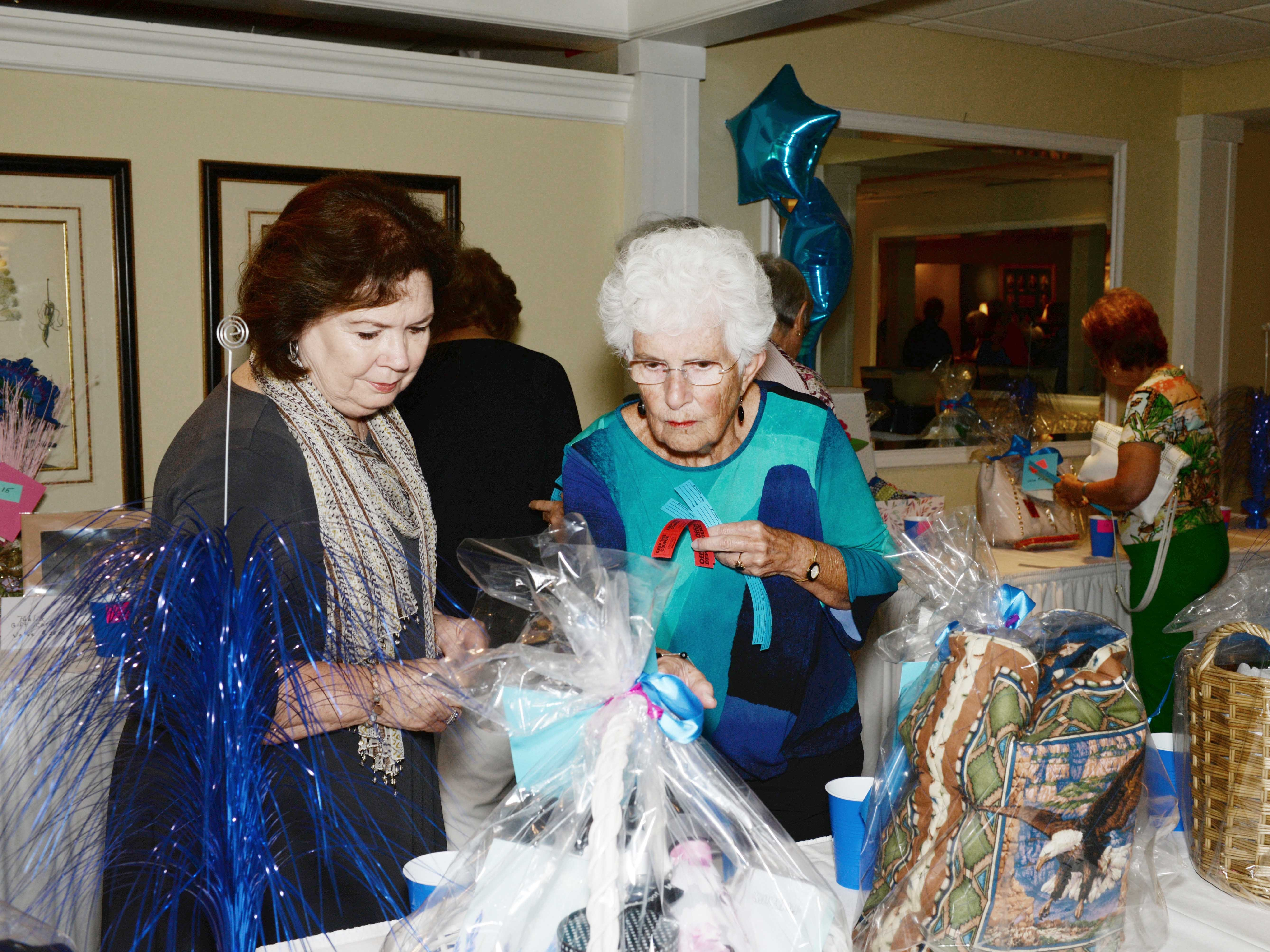 Sara Wilcox, left, and Jane Buss look over the raffle prizes at the American Association of University Women Stuart Branch's 45th anniversary luncheon and fashion show.