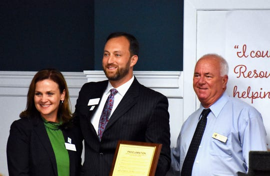 Childcare Resources Executive Director Shannon McGuire Bowman, left, and Board of Directors Immediate Past President Richard Giessert accept a proclamation from County Commissioner Peter O'Bryan.