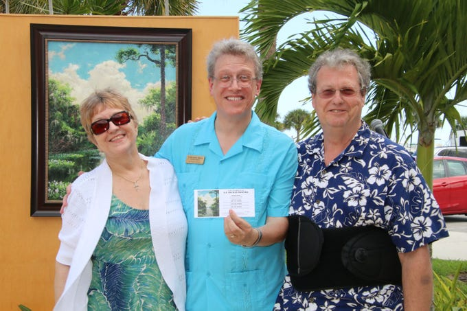 """J. Marshall Adams, center, director of the  A.E. """"Bean"""" Backus Museum & Gallery, with the winning ticket owned by Sandy and Gerald Ludwig at the 23rd annual Backus Brunch at  A.E. """"Bean"""" Backus Museum & Gallery. The Ludwigs won the Backus painting St. Lucie River(c. 1968), valued at $25,000."""