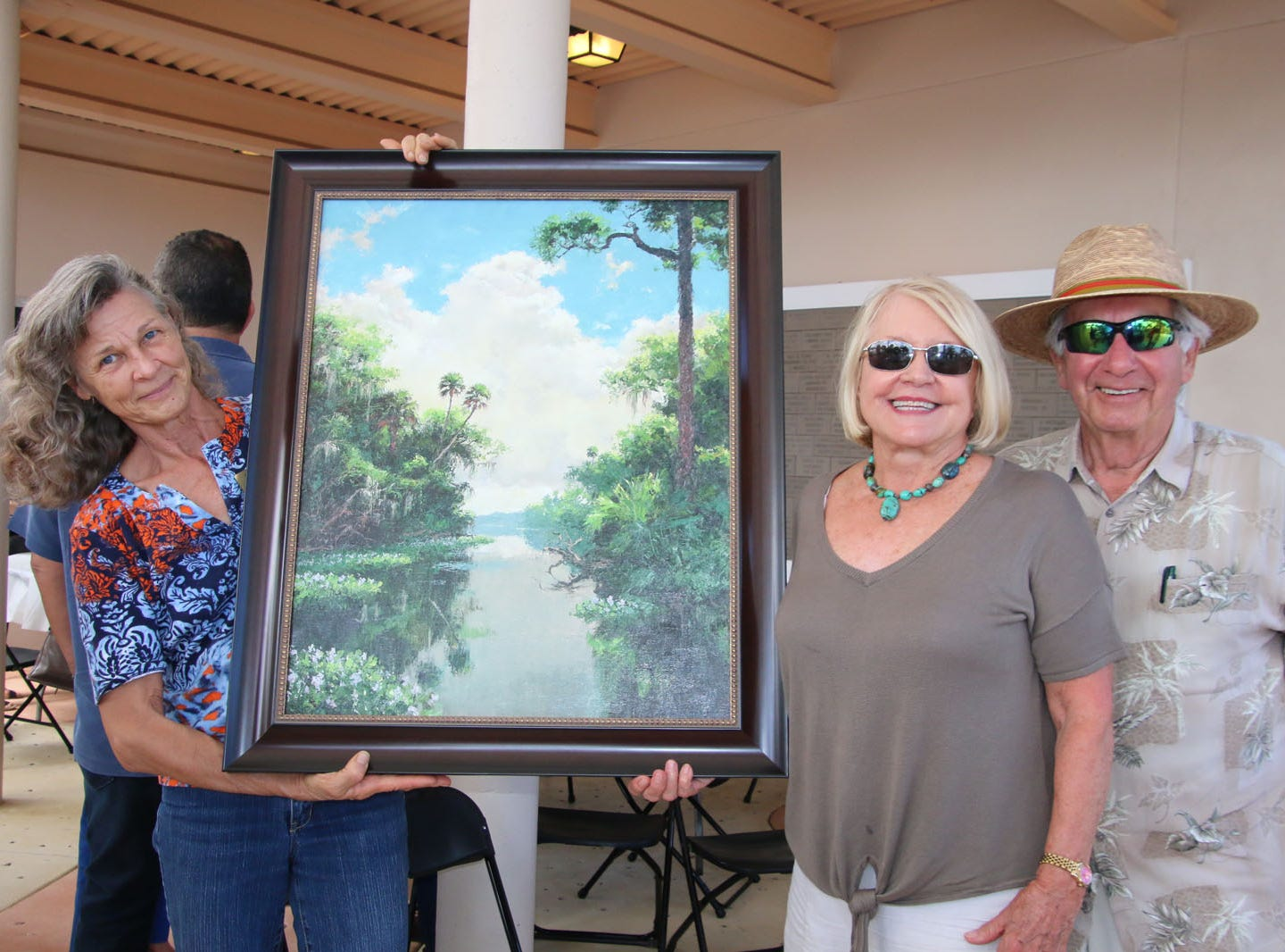 Volunteer Georgina Love, left, holds the Limited Edition Canvas Reproduction won at auction by Joan and Michael Berzansky at the Backus Brunch.