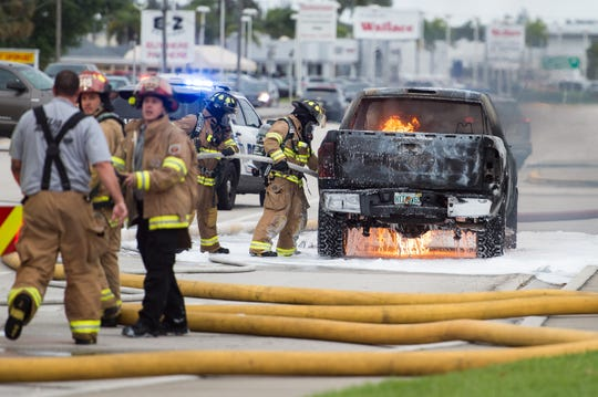 Stuart Fire Rescue personnel work to extinguish a truck that was on fire while on the road Monday, March 18, 2019, in front of Regency Square shopping center on Southeast Federal Highway in Stuart. Stuart Fire Rescue Fire Chief Vincent Felicione said no one was injured in the incident, which required foam to extinguish due to the fuel and vapors. The driver was alerted to the fire while she was driving, according to a witness.