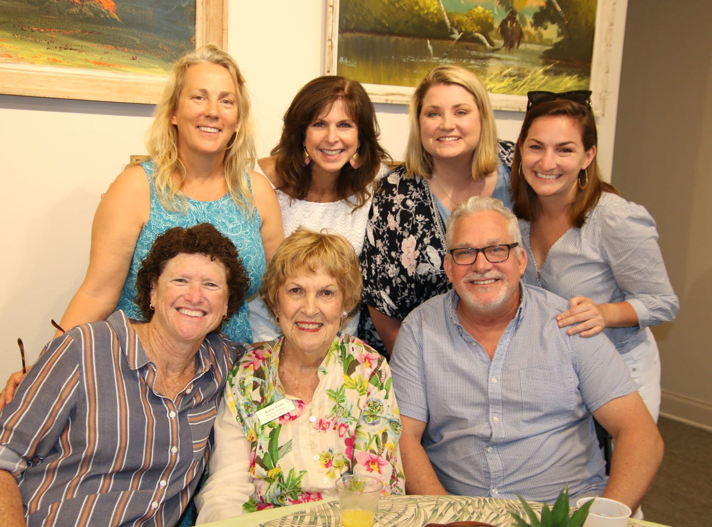 """Kathy Harris Rankine, seated, left, Board of Directors member Katie Enns and Michael Enns, with Meg Enns, standing, Lisa Brown, Amy Carr and Lucie Enns at the Backus Brunch at  A.E. """"Bean"""" Backus Museum & Gallery."""