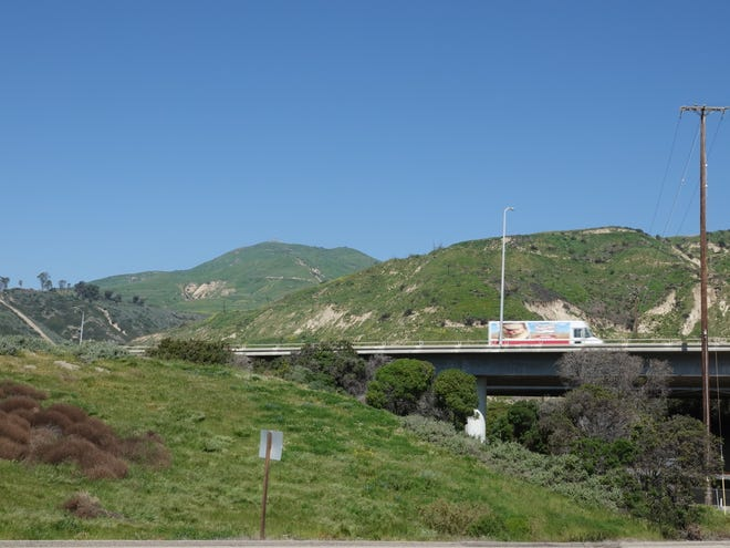 STAR FILE PHOTO Winter rains have greened hillsides along Highway 101 near the Seacliff interchange north of Ventura. Rain continues to fall in the county in mid-May.