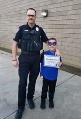 Sgt. Ryan Robison stands beside his nine-year-old son, Jake, who was recognized for saving his classmate and best friend's life.
