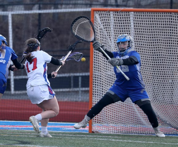 Hendrick Hudson goalie Courtney Gallagher stops a shot by Margaret Flocco of Carmel during a girls lacrosse game at Carmel High School March 19, 2019. Hendrick Hudson defeated Carmel 14-7.