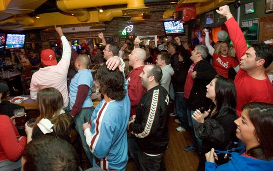 Philadelphia Phillies fans celebrate at Grotto Pizza on Pennsylvania Avenue during the 2008 World Series. The sports bar will welcome former Philadelphia 76er Dikembe Mutombo this weekend as part of its March Madness festivities.