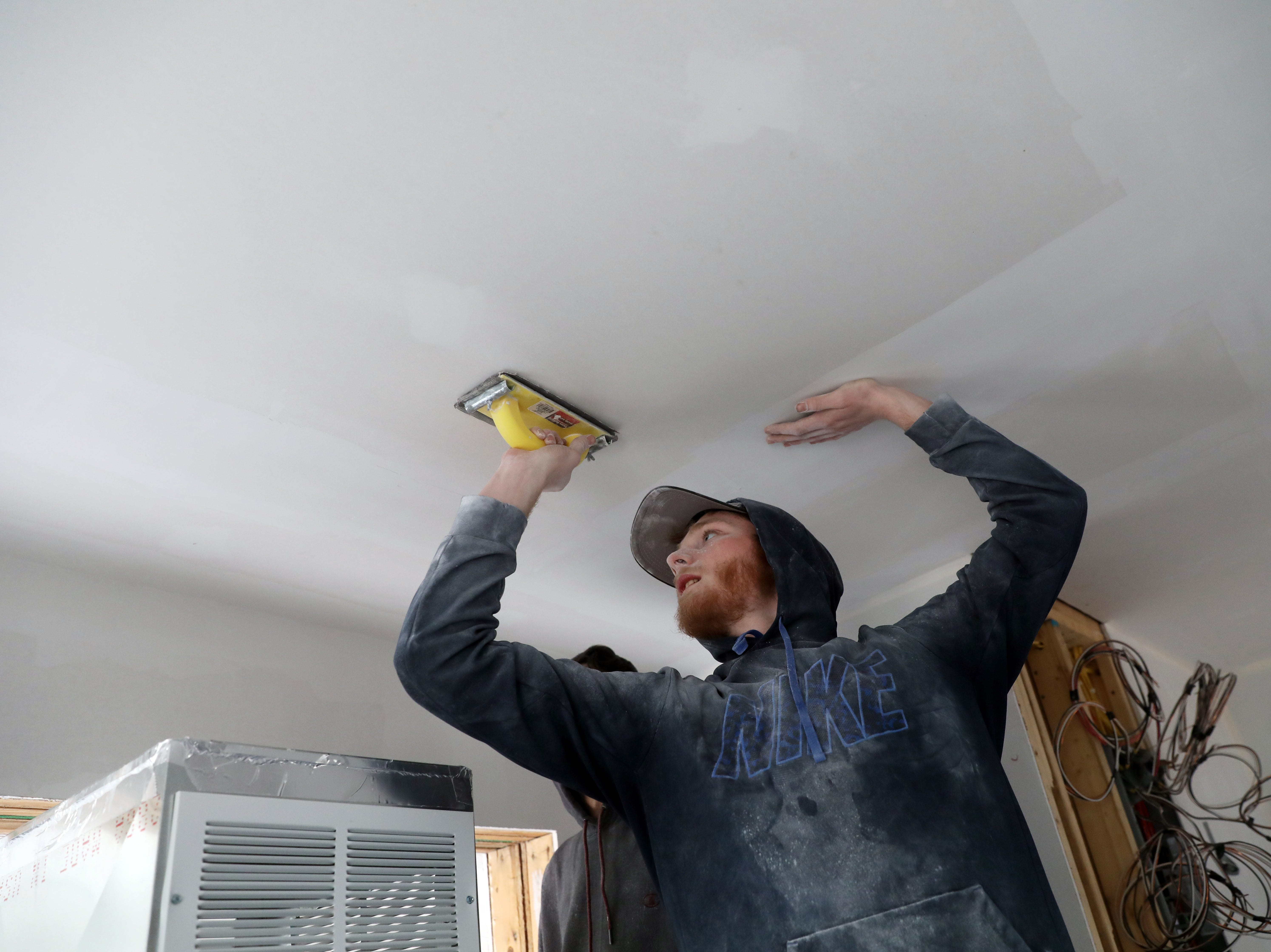 Todd Hina, a Mid-East student from Zanesville Community High School, works on drywall in a house the carpentry program Mid-East Career and Technology Center is building for Habitat for Humanity.
