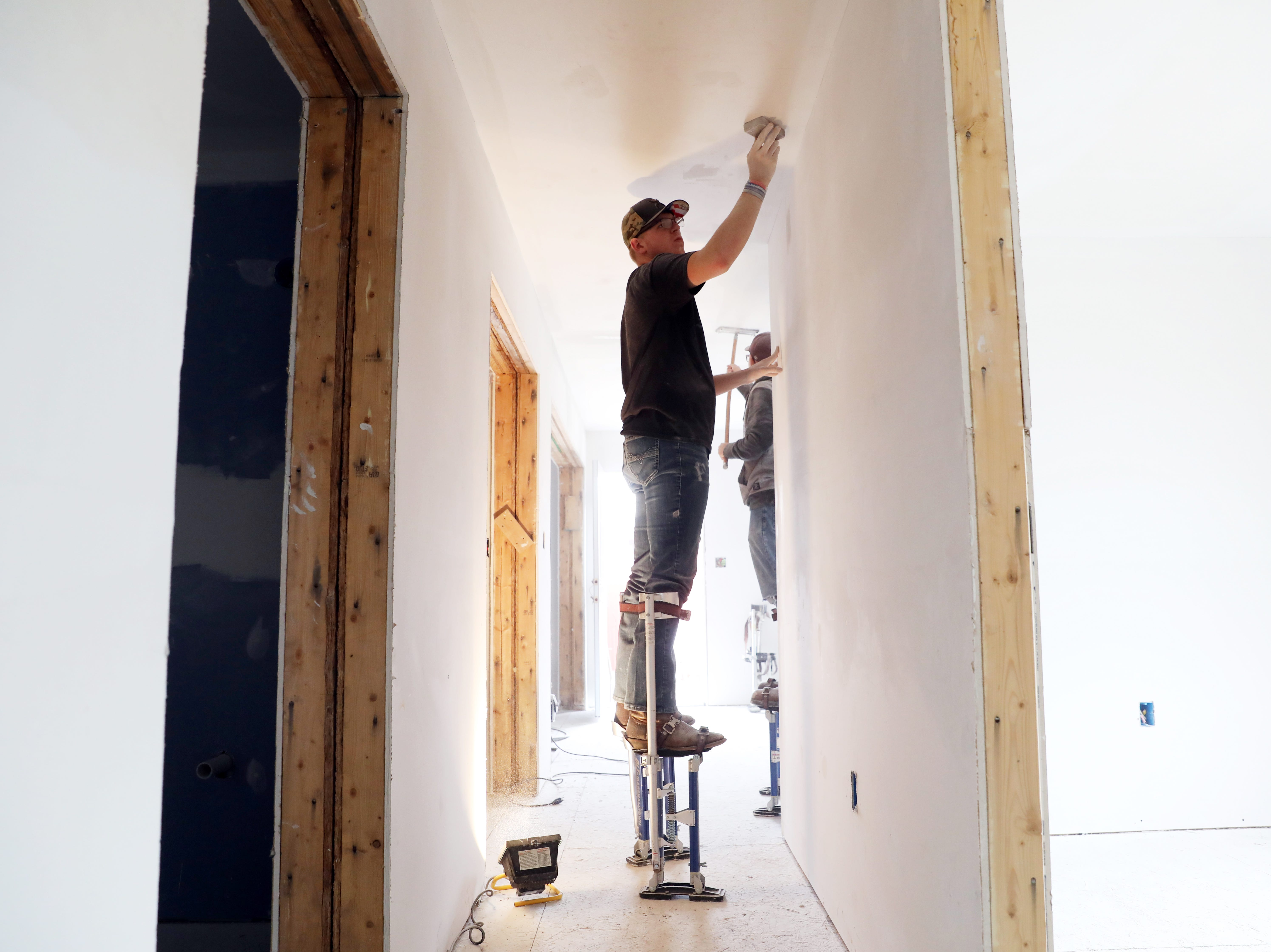 Cole Baker, a Mid-East student from Tri-Valley High School, works on drywall in a house the carpentry program Mid-East Career and Technology Center is building for Habitat for Humanity.