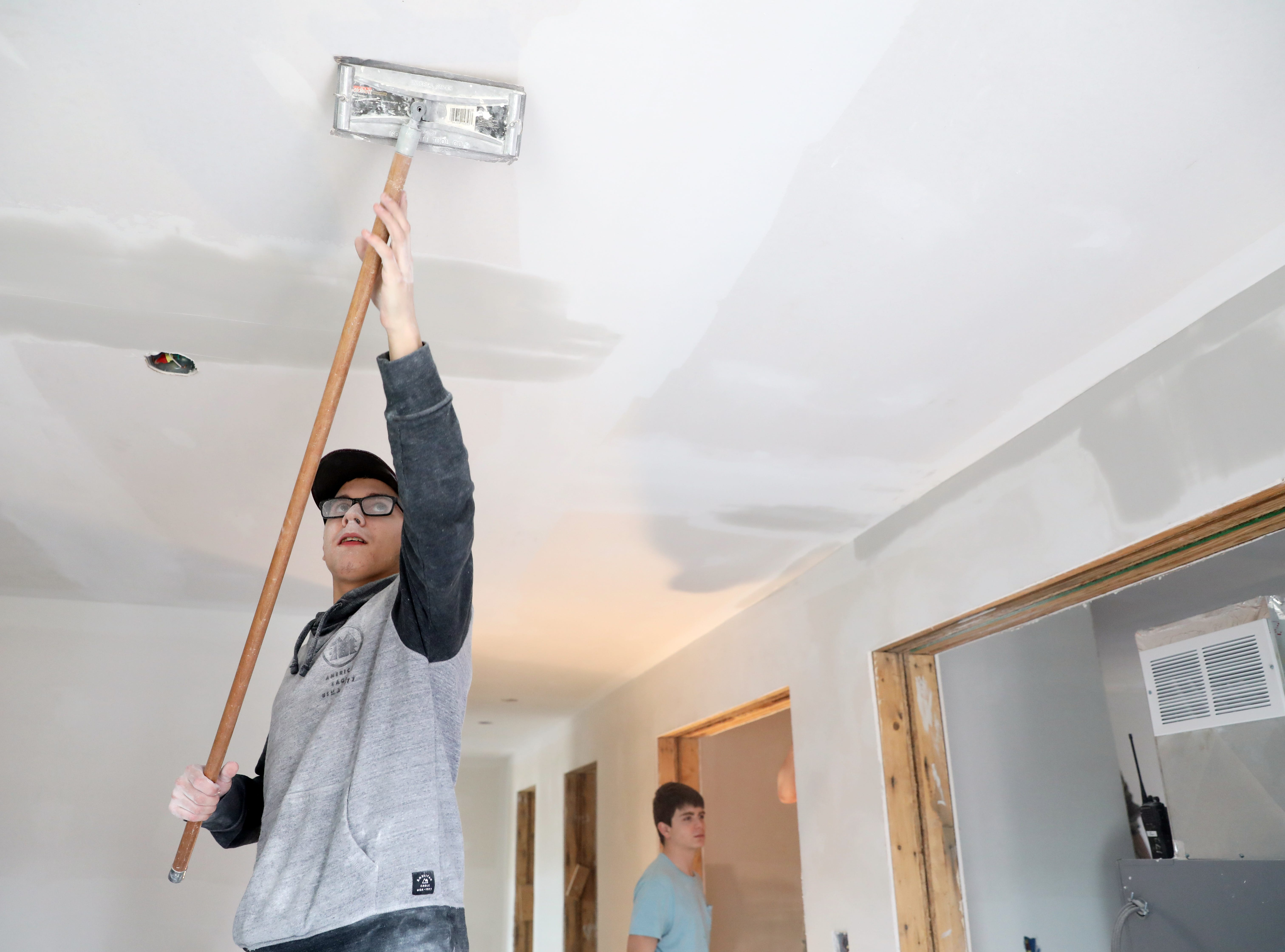Colton Woodward a Mid-East student from John Glenn High School, works on drywall in a house the carpentry program Mid-East Career and Technology Center is building for Habitat for Humanity.