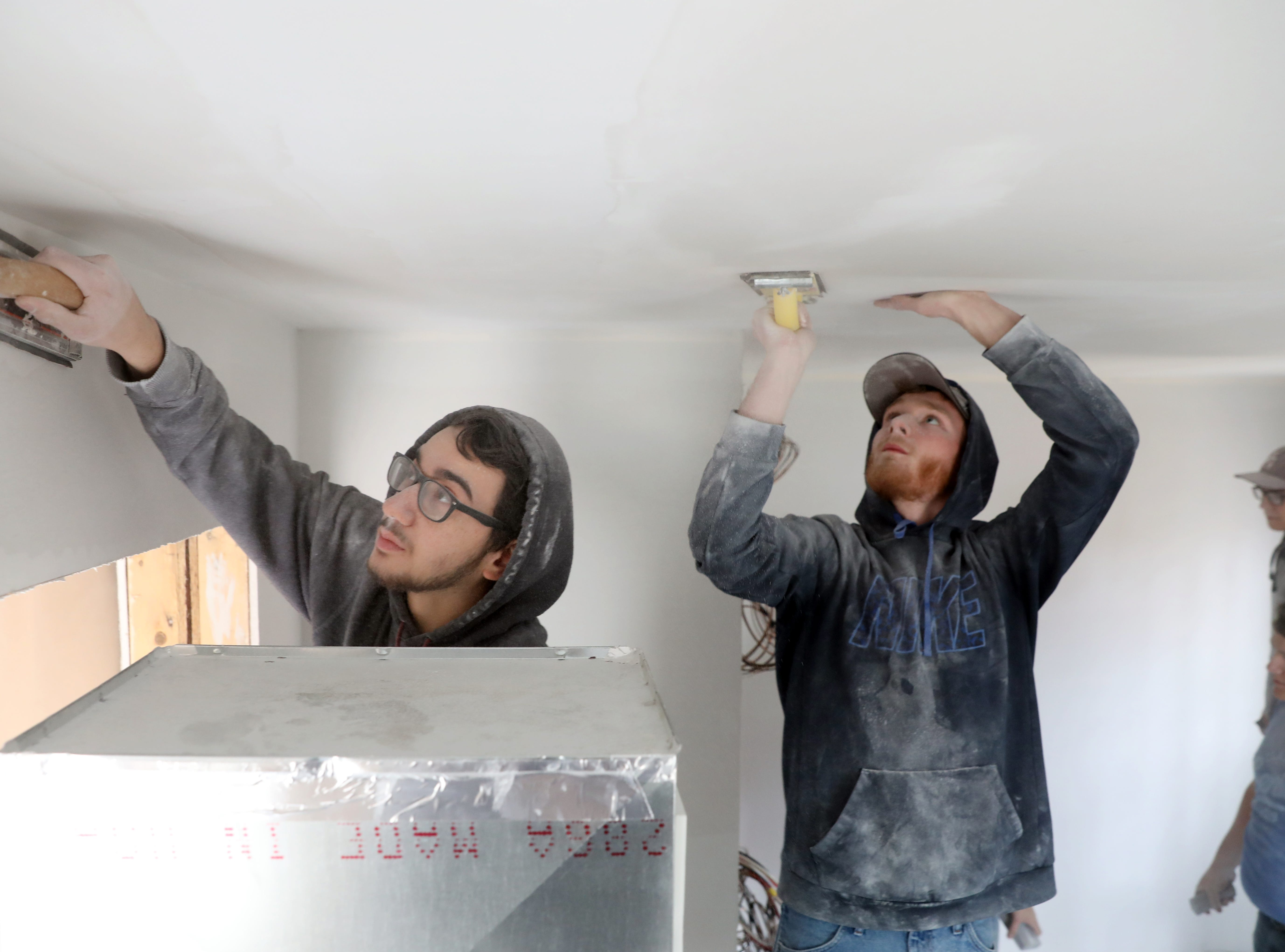Dustin Wallace, left, and Todd Hina work on the ceiling in a house the carpentry program Mid-East Career and Technology Center is building for Habitat for Humanity.