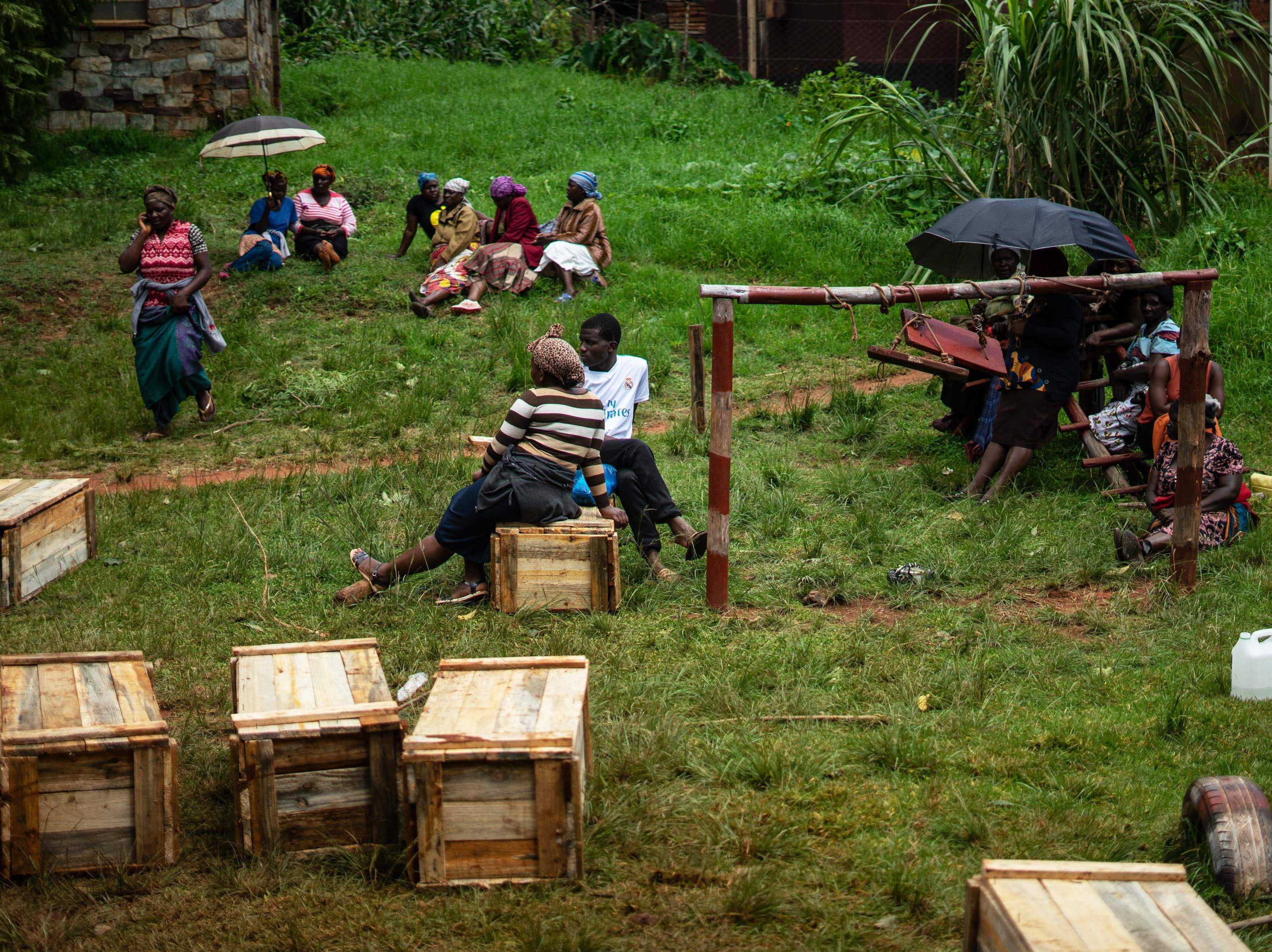 Relatives sit beside their family members' coffins outside St. Thomas Catholic Church in Chimanimani, Zimbabwe, waiting for transport to the grave site on March 18, 2019.