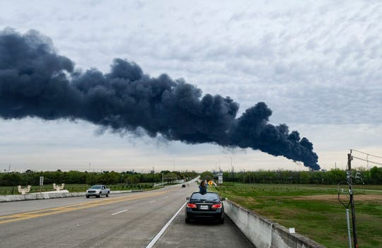 Debra Wilson photographs a plume of smoke from a petrochemical fire at Intercontinental Terminals Company in Deer Park out of her sunroof on Monday. The fire has been burning since Sunday afternoon.