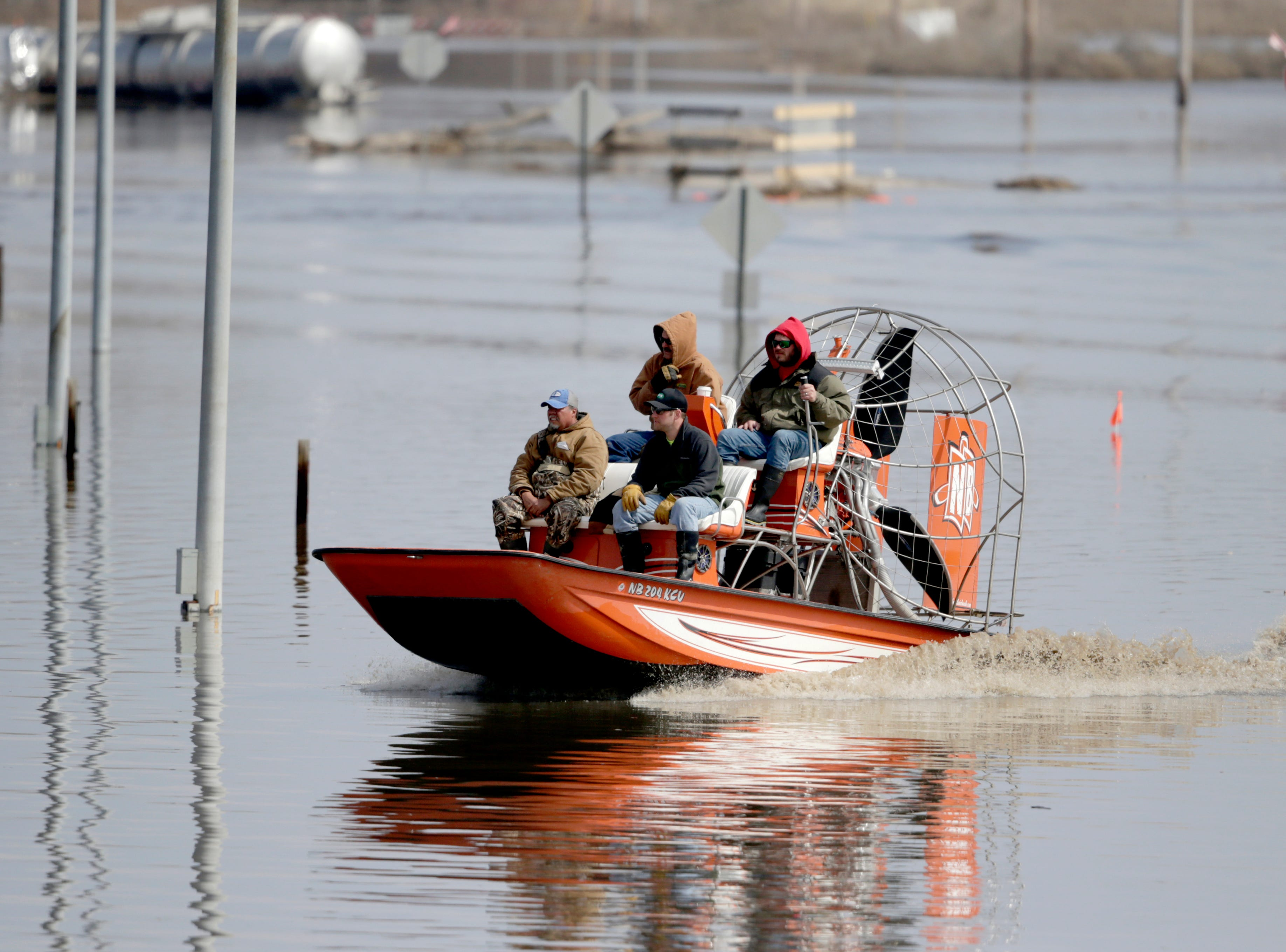 Gabe Schmidt, owner of Liquid Trucking, back right, travels by air boat with Glenn Wyles, top left, Mitch Snyder, bottom right, and Juan Jacobo, bottom left, as they survey damage from the flood waters of the Platte River, in Plattsmouth, Neb., on March 17, 2019.