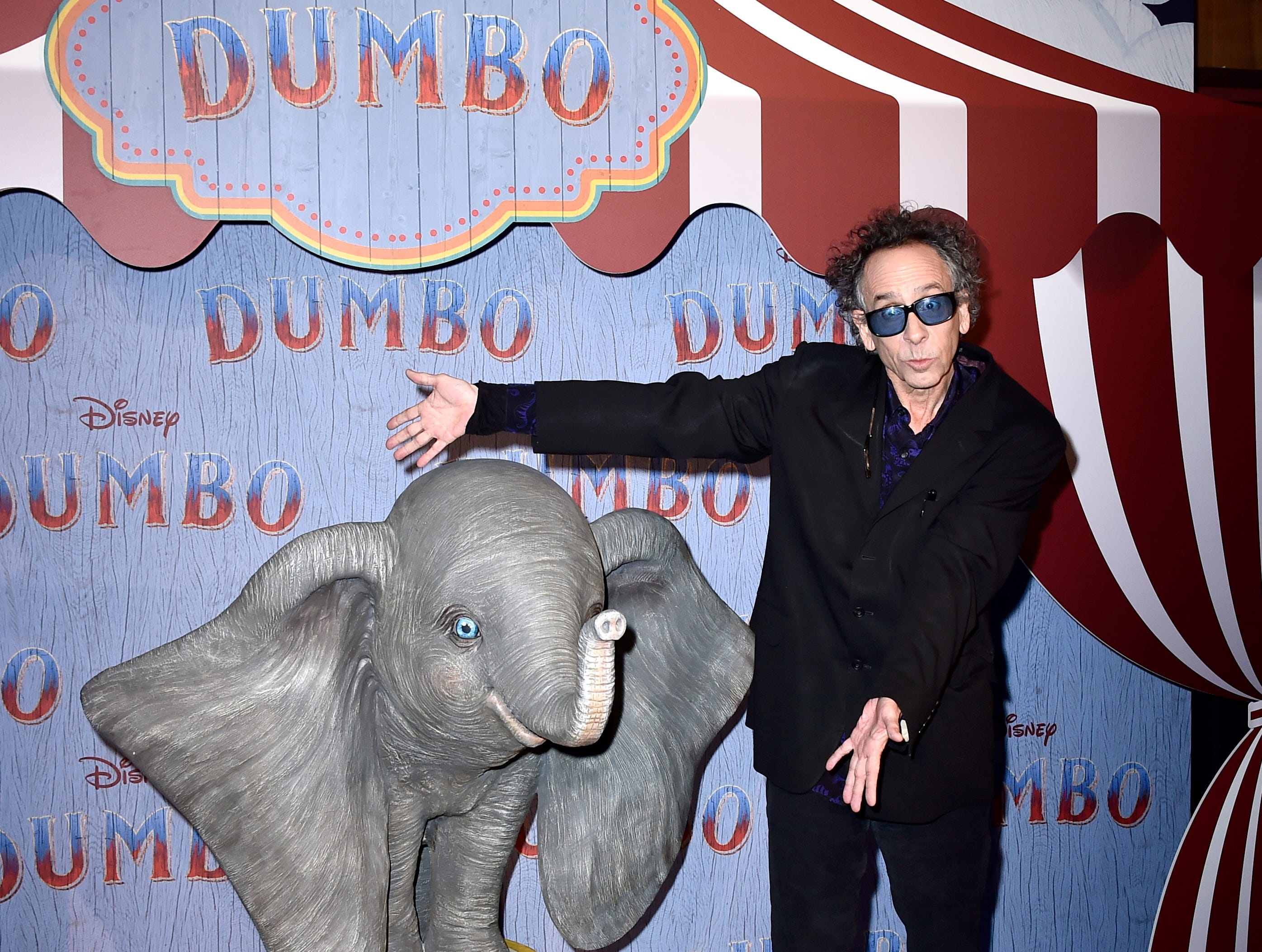 "Director Tim Burton shows off the real star of the Paris premiere of the live-action remake of ""Dumbo"" on March 18, 2019."
