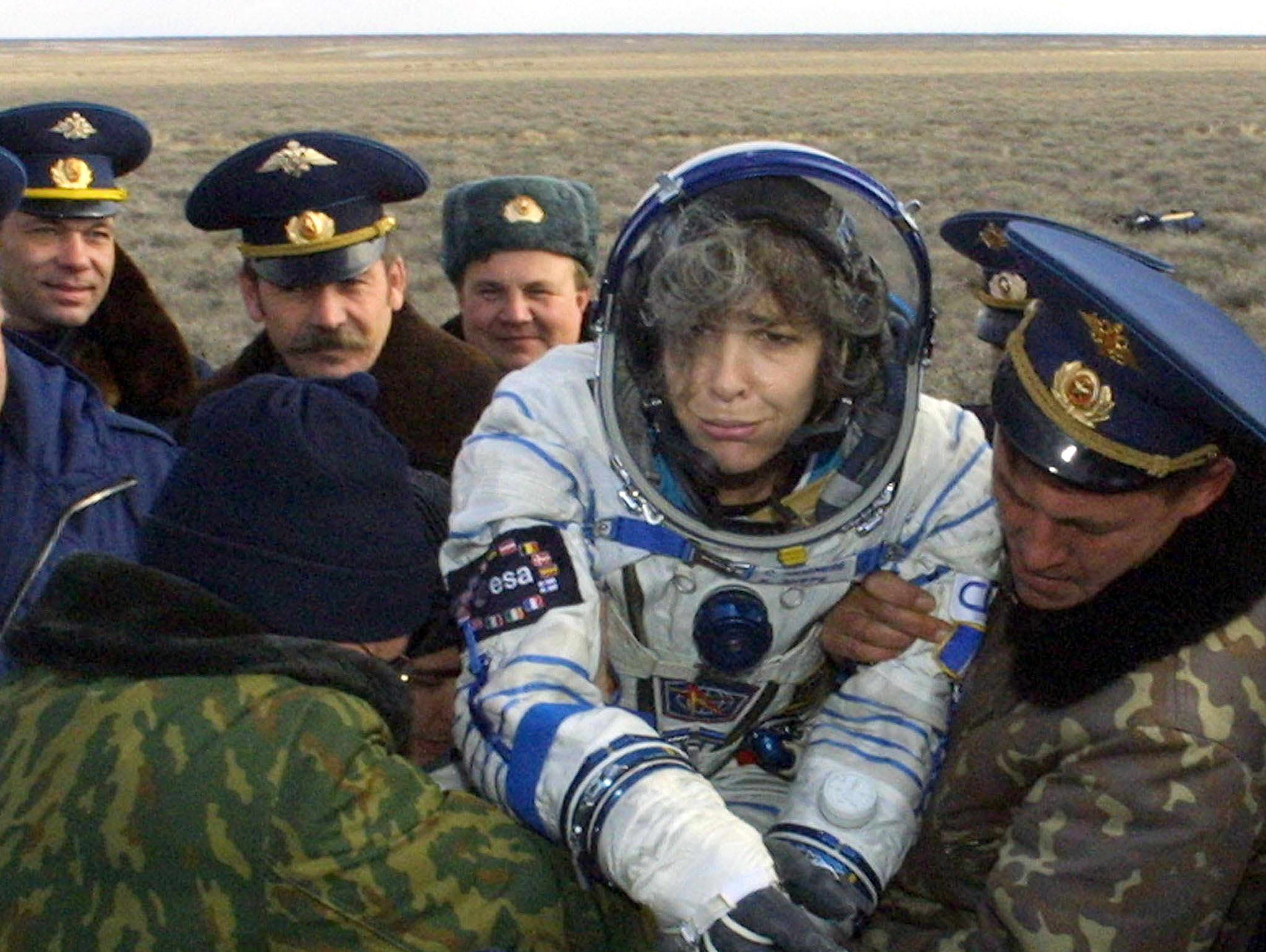 Officials of the Russian search and rescue service help French astronaut Claudie Haignere upon her landing in Kazakhstan, Oct. 31,  2001, after a mission on the International Space Station. Haignere, the first European woman on the international space station, and her two Russian teammates returned safely to earth in Kazakhstan.