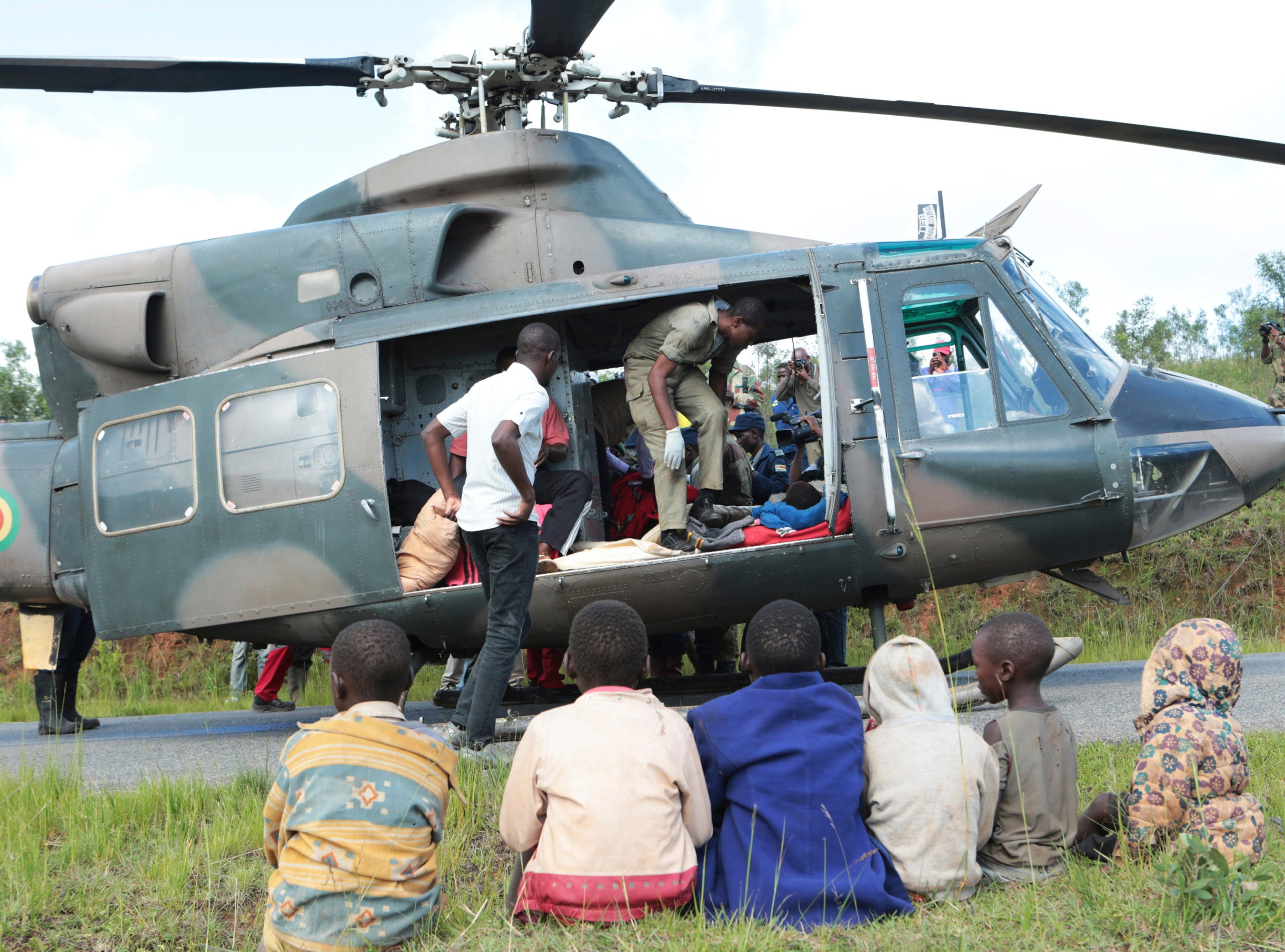 Soldiers and paramedics carry injured survivors from a helicopter in Chimanimani, Zimbabwe on March, 19, 2019.