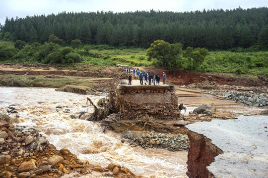 Timber company workers stand stranded on a damaged road on March 18, 2019, in eastern Zimbabwe after the area was hit by Cyclone Idai. Idai tore through the centre of Mozambique on March 14 before barreling into neighboring Zimbabwe, bringing flash floods and ferocious winds and washing away roads and houses. Over 1,000 people are feared dead.