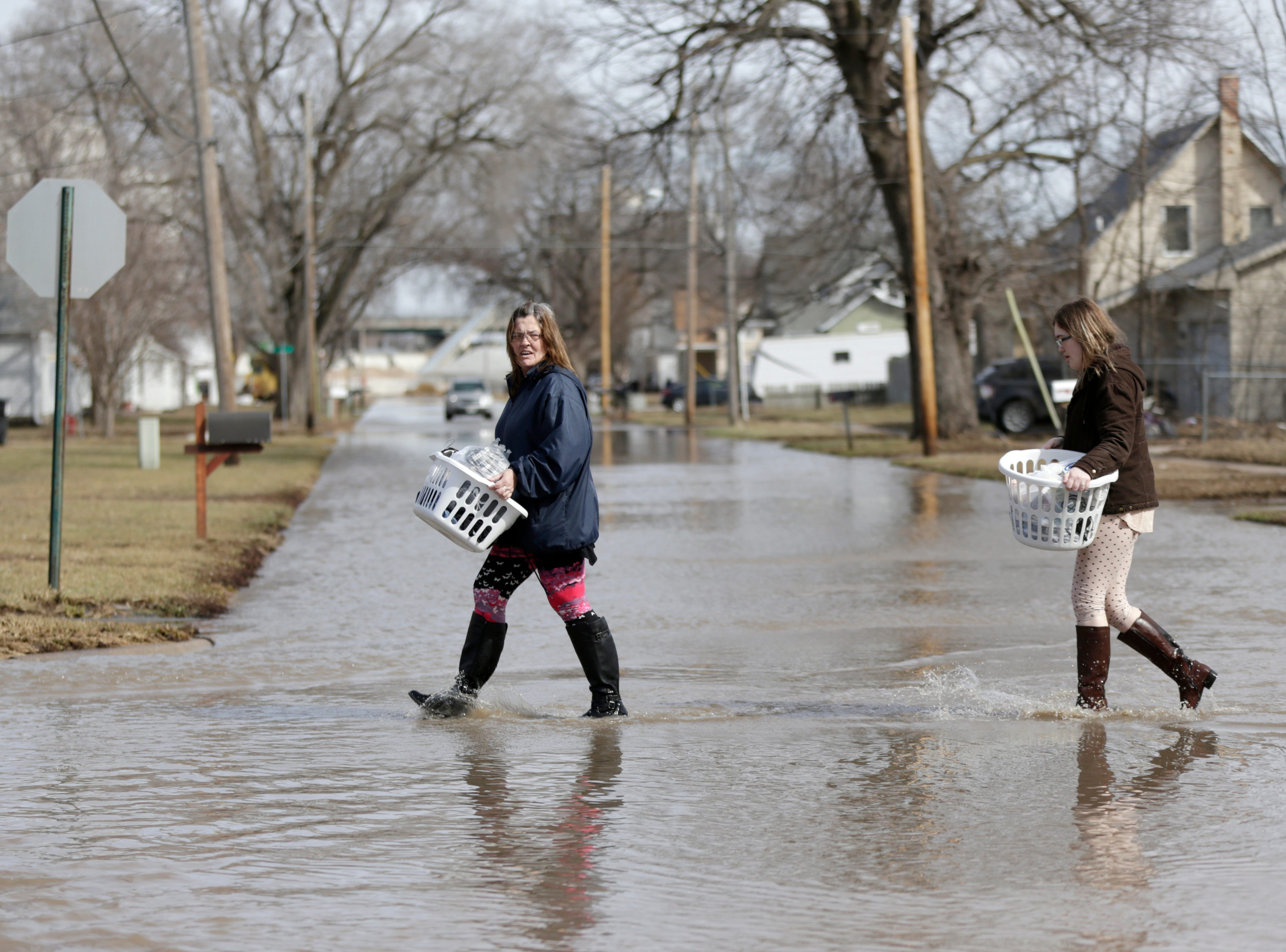 Akashi Haynes, left, and her daughter Tabitha Viers carry their belongings rescued from their flooded home in Fremont, Neb., on March 18, 2019.