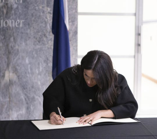 The Duchess of Sussex signs a book of condolence on behalf of the royal family.