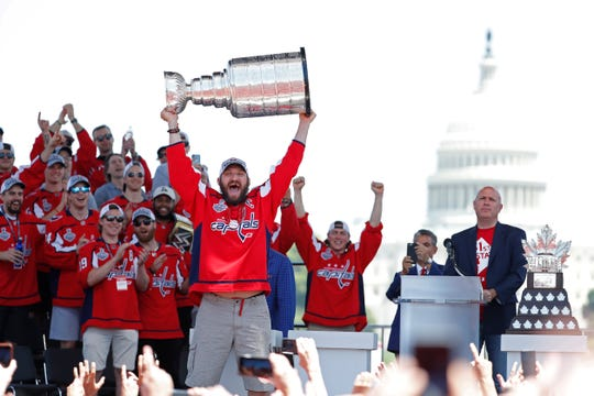 Washington Capitals left wing Alex Ovechkin lifts the Stanley Cup during the team's championship parade and celebration on the National Mall.