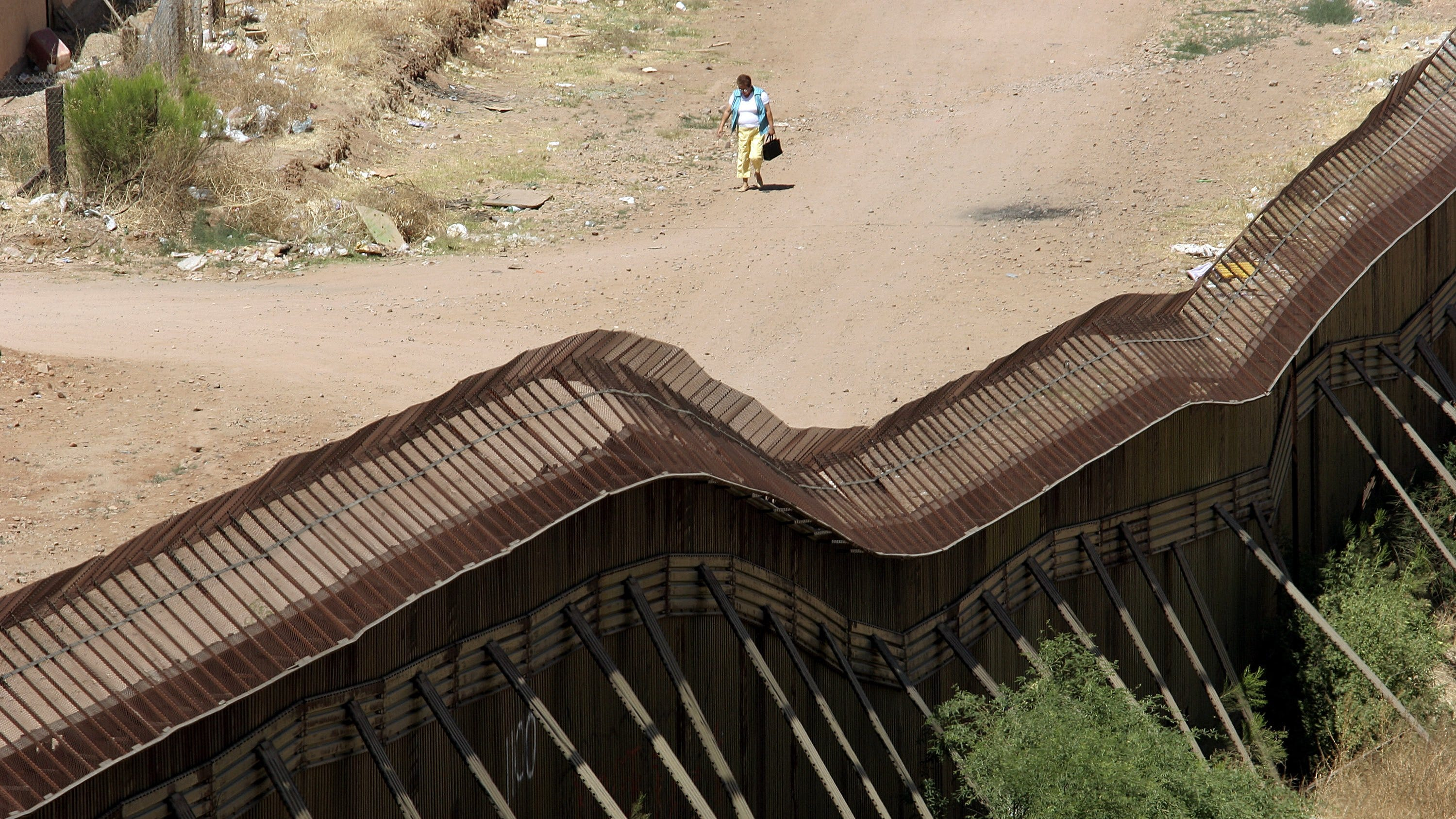 A woman walks along a dirt road on the Mexican side of the border.
