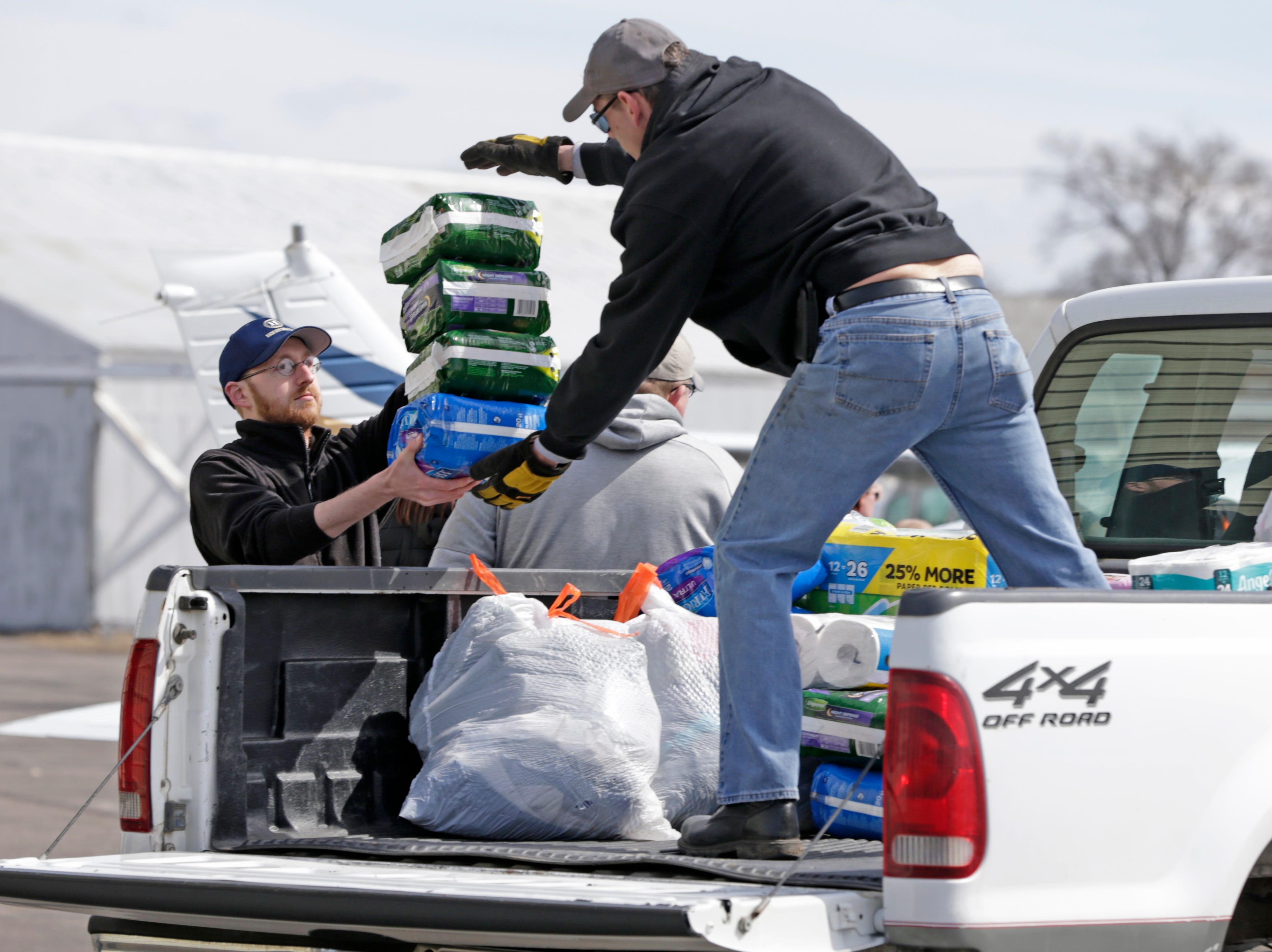 Volunteers load supplies flown in to the Fremont, Neb., airport by volunteer pilots, on March 18, 2019. Walled off by massive flooding, Fremont is getting a big lift from private pilots who are offering free flights to shuttle stranded residents to and from their hometown. Authorities say flooding from the Platte River and other waterways is so bad that just one highway lane into Fremont remains uncovered, and access to that road is severely restricted. Airport officials estimate that more than 500 people have caught flights on small aircraft flown by volunteers.