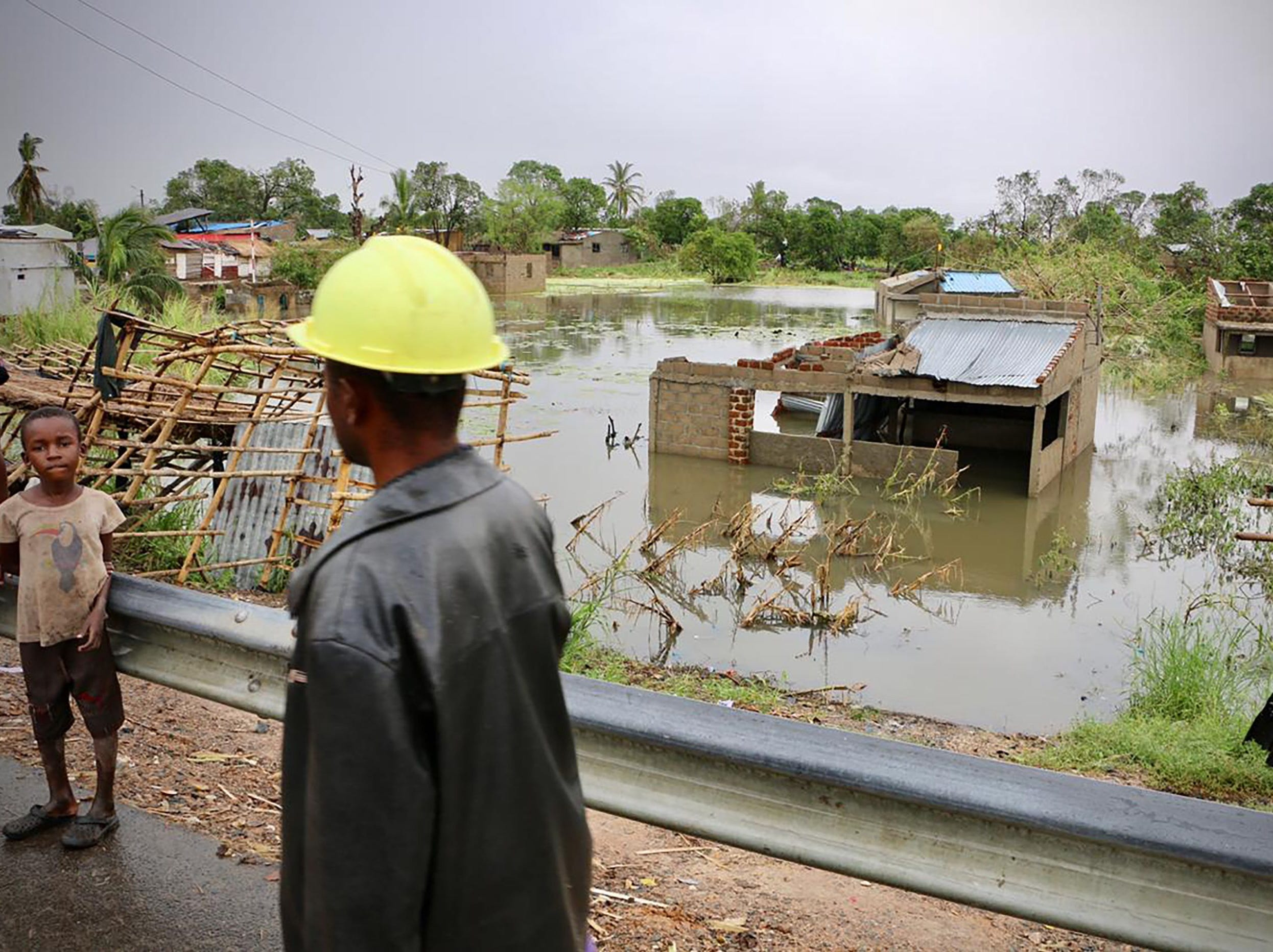 Locals stand near the flooded village of Tica in central Mozambique, on March 19, 2019, after the area was hit by the Cyclone Idai. Rescue workers in Mozambique were racing against time to pluck people off trees and rooftops, after a monster storm reaped a feared harvest of more than 1,000 lives before smashing into Zimbabwe.