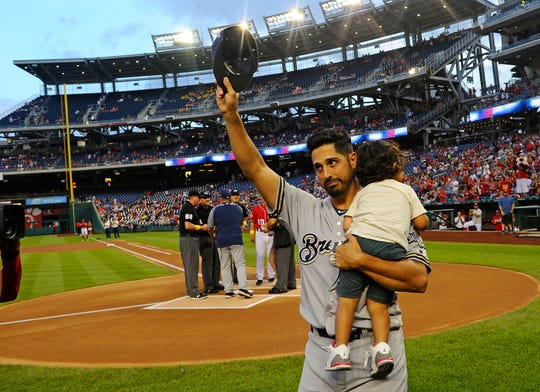 Milwaukee Brewers pitcher Gio Gonzalez holds his son, Enzo, after being honored before a game against his former team, the Washington Nationals, in September.