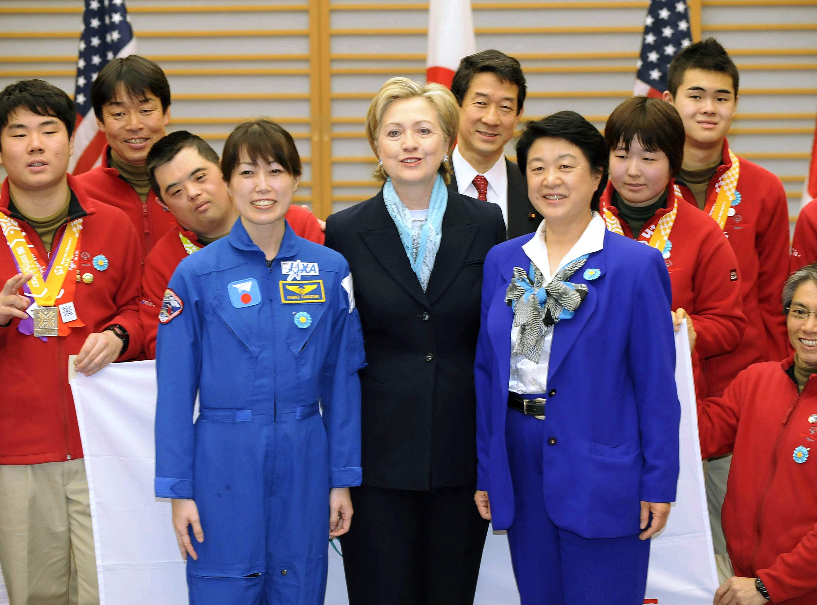 Secretary of State Hillary Rodham Clinton, center, poses with Naoko Yamazaki, left in blue, the second Japanese woman to go into space, and Chiaki Mukai, right in blue, the first Japanese female astronaut, and athletes of the Special Olympics World Winter Games during a reception after her arrival at Haneda international airport in Tokyo, Japan, Monday, Feb. 16, 2009.