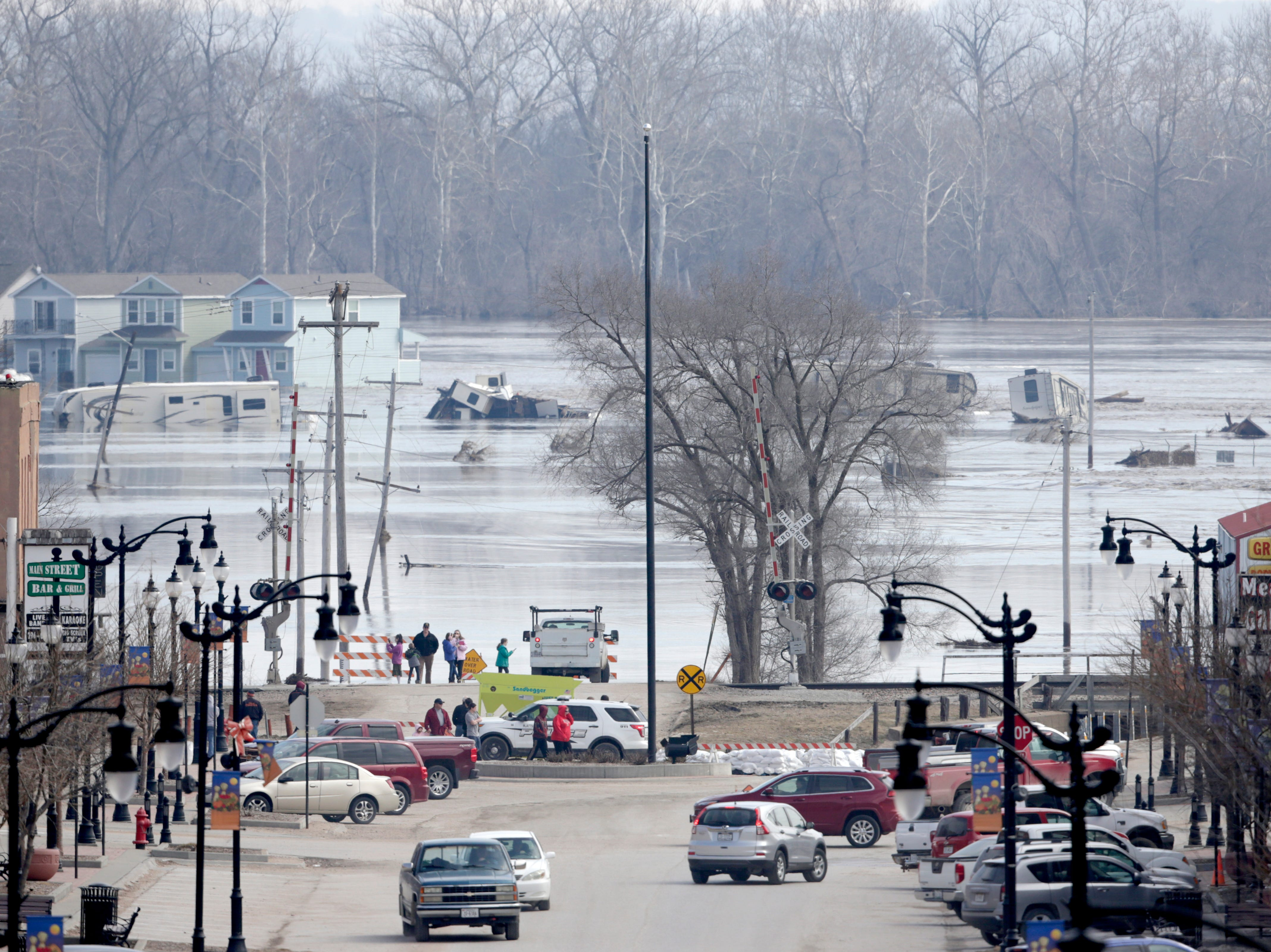 People watch the rising waters from the Platte and Missouri rivers which flooded areas of Plattsmouth, Neb., on March 17, 2019.