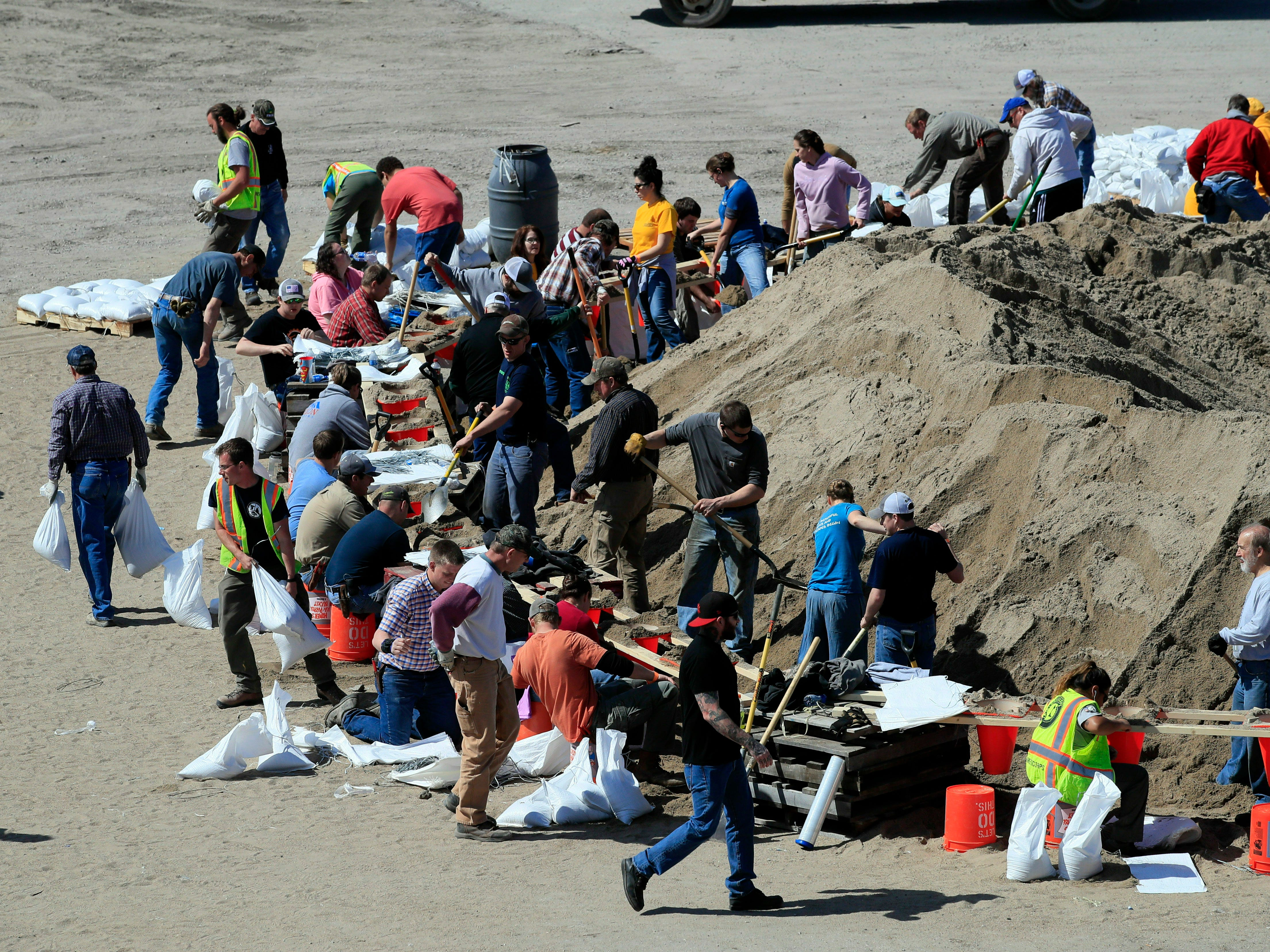 Volunteers fill sandbags in preparation for flooding along the Missouri River in St Joseph, Mo. on March 18, 2019.