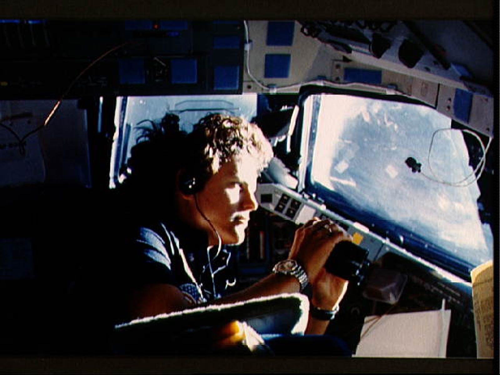 Astronaut Kathryn D. Sullivan, 41-G mission specialist, uses binoculars for a magnifed viewing of earth through the forward cabin windows in 1984. Dr. Kathy Sullivan is the first American woman to walk in space aboard shuttle mission STS-41G.