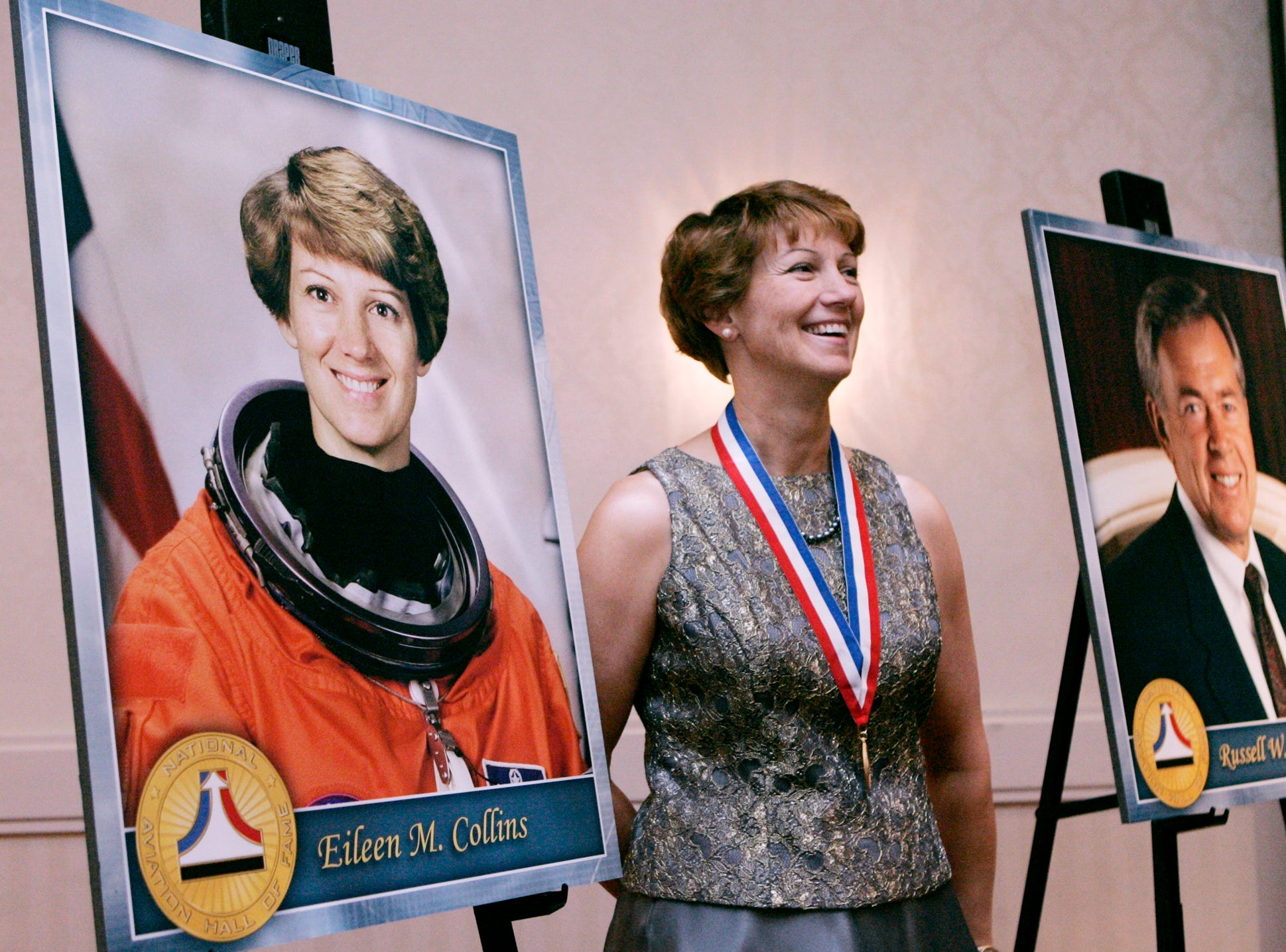 Eileen Collins stands next to a portrait of herself as she has her picture taken Saturday July 18, 2009 at the National Aviation Hall of Fame photo reception. The event was held for aviation figures who are to be enshrined in the organization's hall of fame. Collins, born in Elmira, N.Y., was the Air Force's first female flight instructor and was chosen to be an astronaut in 1991. In 1995, she became the first woman to pilot a space shuttle, and she became the first to command an American space mission when she served on a shuttle in 1999. She flew four shuttle missions, logging 872 hours before retiring in 2006.