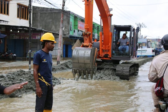This handout picture taken and released by Indonesia's Badan Nasional Penanggulangan Bencana (BNPB), the accident mitigation agency, on March 19, 2019 shows workers clearing a road after flash floods in Sentani.