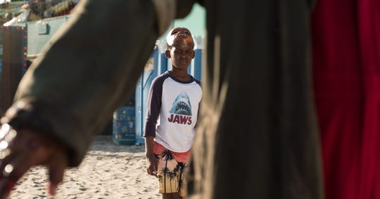 "Jason Wilson (Evan Alex) sees something seriously creepy on the beach in Jordan Peele's ""Us."" The ""Jaws"" shirt is a nod to one of Peele's biggest influences, Steven Spielberg."