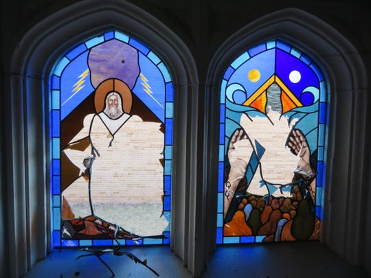 Two of the stained glass windows broken at All Saints Episcopal Church in Appleton late Monday night.
