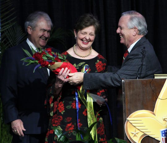 Former mayor and 2009 Distinguished Citizen Award winner Norm Archibald, right, presents flowers to Rae Ann Hamilton. Hamilton and her husband, Lee (left) were honored Tuesday night by the Boy Scouts of American Texas Trails Council. Archibald said Rae Ann Hamilton deserved flowers for going to camp while growing up in a Scouting family.