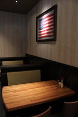 A framed United States flag overlooks two tables near the kitchen at Cheddar's. On the opposite wall is a Texas flag; the state flag is displayed wherever there is a restaurant - that's 23 states.
