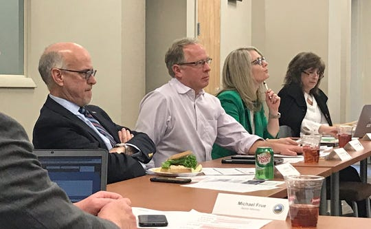 Buncombe County Board of Commissioners Chairman Brownie Newman, center, and commissioners Joe Belcher, left, and Amanda Edwards, right, listen in during a March 19 meeting of the county's Affordable Housing Committee.