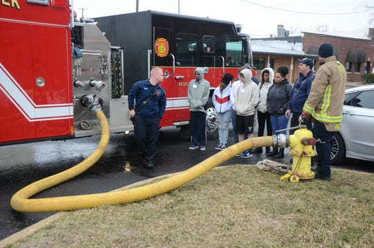 Battle Creek firefighters demonstrate how they attach fire hoses to the engines.